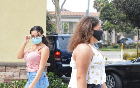 Two women wearing masks walk past each other. One of the women is turning her head to get a second look at the other one.