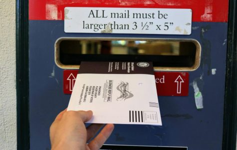 A student submits their ballot in the Mail Center's drop box.