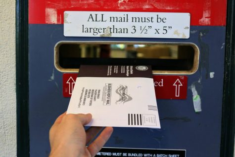 A student submits their ballot in the Mail Center